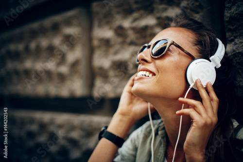 Poster de jardin Magasin de musique Happy young woman listening to music via headphones on the street on a sunny day