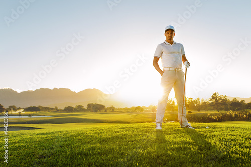 Poster Golf Young male golfer standing on golf course on a summer day