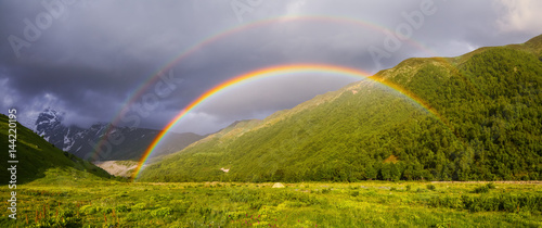Foto op Aluminium Heuvel Colorful rainbow among high mountains.
