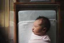 Overhead View Of Newborn Baby Girl Sleeping In Crib At Hospital