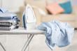 Leinwandbild Motiv Electric iron and pile of clothes on ironing board