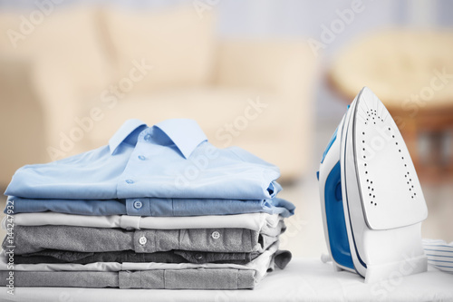 Fotografie, Obraz Electric iron and pile of clothes on blurred background