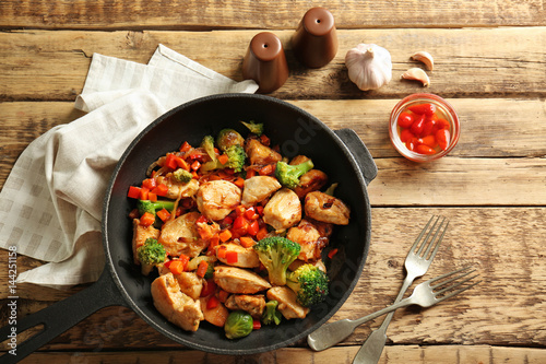 Chicken stir fry with cutlery and spices on table