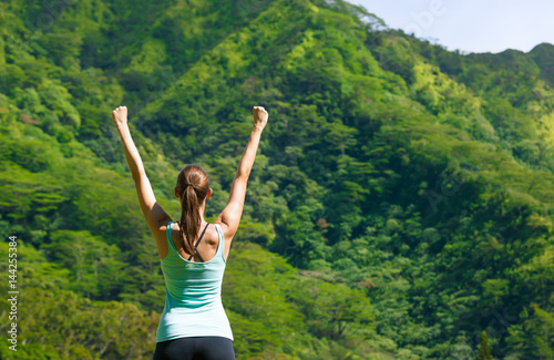 Active healthy lifestyle and fitness goals concept. Fit woman celebrating against a beautiful nature setting.