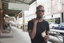 Young Man Holding Ice Cream While Standing On Sidewalk