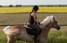A Young Woman Riding A Horse H...
