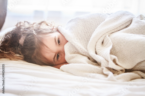indoor portrait of young child girl wrapped in blanket Canvas Print