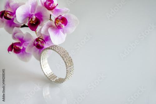 Valokuva  Zirconium bracelet lies on the background of purple orchids