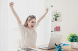 Leinwandbild Motiv Yes! Happy excited woman at home workstation triumphing with raised hands