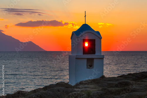 Small greek chapel and mount Athos at sunrise or sunset and sea panorama in Gree Canvas Print