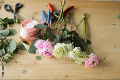 Foto op Canvas Bloemen Florist at work: pretty young woman making fashion modern bouquet of different flowers
