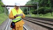 Railway employee in yellow uniform with tablet computer stands on railway line. Railway worker makes notes in his tablet computer. Railway worker in uniform and white hard hat with tablet pc in hands
