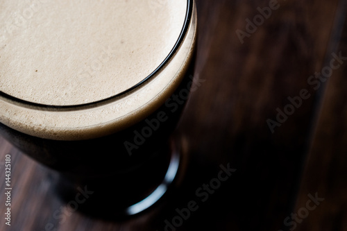 Fotografia Dark Beer on wooden surface.