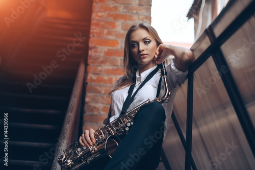 Plakát  Young attractive girl standing in white shirt with a saxophone - outdoor in old town