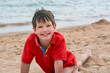 Cute little boy lies on the sand on the seashore happy