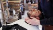 barber applying aftershave lotion to male neck