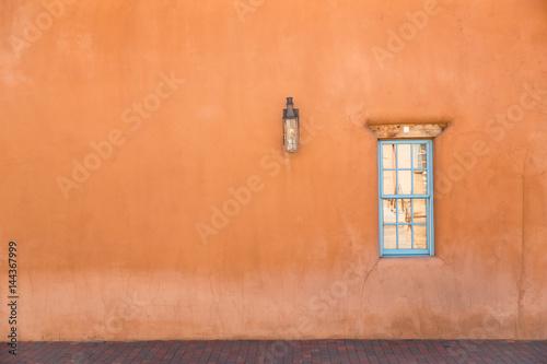 Fototapeta premium pomarańczowa ściana z turkusowym oknem w Santa Fe w Nowym Meksyku