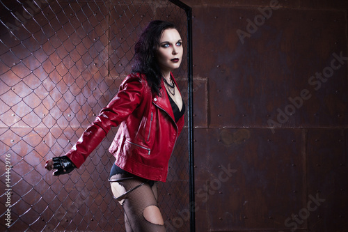 Fotografía  Aggressive punk woman with a bat, in red leather jacket
