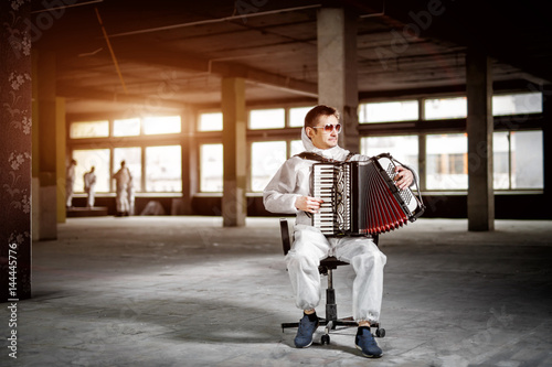 Fotografie, Tablou  The musician playing the harmonica, accordion in the hall with columns