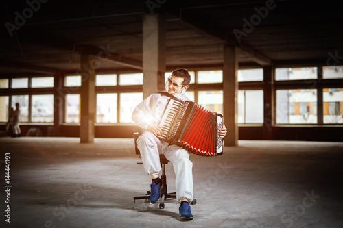 The musician playing the harmonica, accordion in the hall with columns Tapéta, Fotótapéta