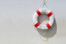 Old Life Buoy Hanging On White Concrete Wall