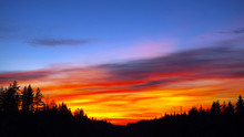 Blazing Sunset Over The Evening Hills Forest. Flaming Sky - The Landscape In The Setting Sun.