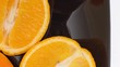 Close-up of a delicious oranges in black plate zooming