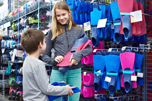 Photo  Children choose swim fins in sports shop