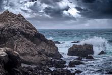 Foggy View Of Pebble Beach California Coast With Storm Clouds And Rough Seas Causing Waves To Crash On Rocks. The Beach Is Shaped By Erosion And Climate Change.