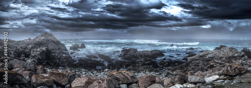 Foto op Plexiglas Kust Foggy view of Pebble Beach California coast with storm clouds and rough seas causing waves to crash on rocks. The beach is shaped by erosion and climate change.
