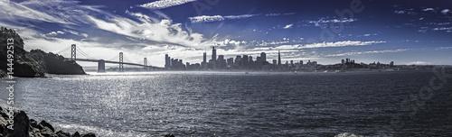 Plakat Panorama San Francisco i Bay Bridge. Widok miejski pokazuje budynki dzielnic biznesowych i drapacze chmur oraz Ocean Spokojny. Obraz przedstawia turystykę w Ameryce.