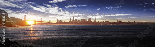 Panorama of downtown San Francisco and the Bay Bridge. The urban view shows business district buildings and skyscrapers and the pacific ocean. The image depicts tourism in America.