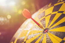 Red Dart Arrow In The Center Of Dartboard. Blur And Bokeh In Sunrise Time Background