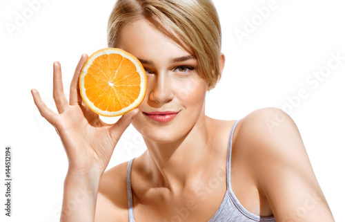 Fotografía  Lovely girl holding a slice of orange in front of her face and smiling
