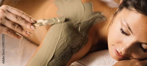 Fotografía  The girl enjoys mud body mask in a spa salon. Luxury treatment.
