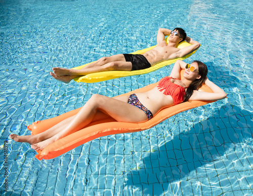Obraz na plátně  young couple relaxing on inflatable raft at swimming pool.