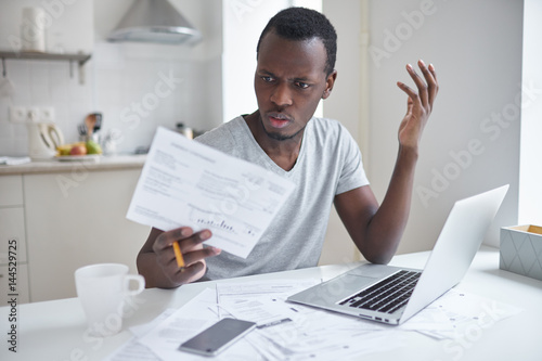 Fotografija  Indignant angry irritated african american male sitting at kitchen table, looking at papers in shock, astonished with amount of unpaid bills
