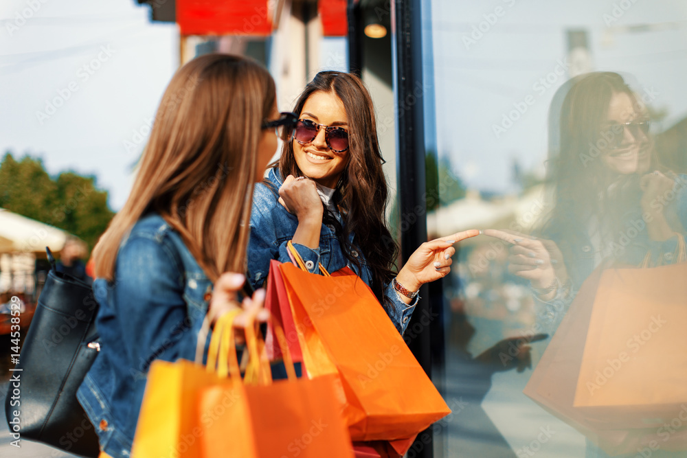 Fototapety, obrazy: Two young women in shopping looking at shop window in the city