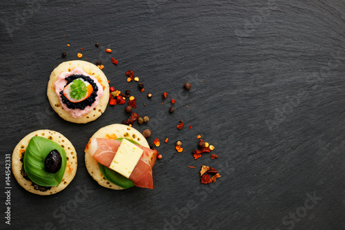 Tela Homemade pancake canapes on slate stone plate for finger food party