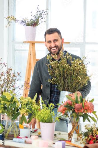 Fototapeta Florist at work: the young MAN making fashion modern bouquet of different flowers obraz na płótnie