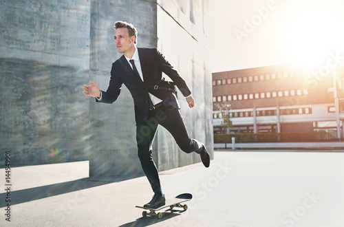 Confident skater wearing suit riding in city Tapéta, Fotótapéta