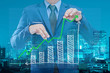 business man try to bring graph up with night modern city building background , business concept