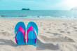 Colorful flip flops on beach against sunny sky.