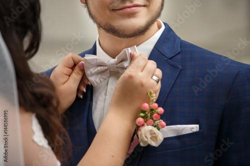 Fotografie, Obraz  Bride holding groom's bow tie at wedding day