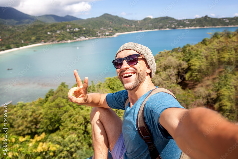 Fototapeta Young male hipster traveler doing selfie overlooking the tropical sea. Adventure, vacation, wonderlust, internet, technology concept.