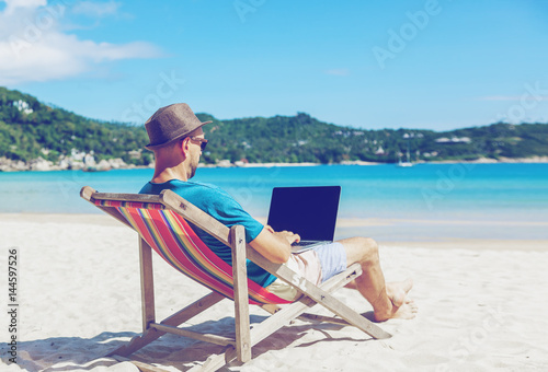 Young hipster man with laptop on tropical beach Fototapeta