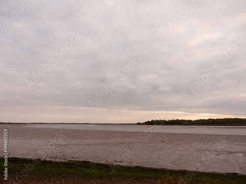 Photo  Low tide summer sky nightfall grey clouds mood and reds with river running throu