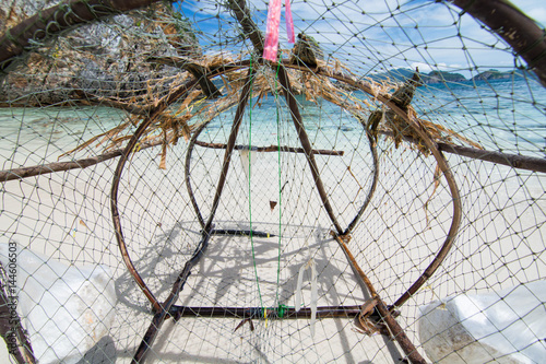 Fish trap and garbage aground on the beach Wallpaper Mural
