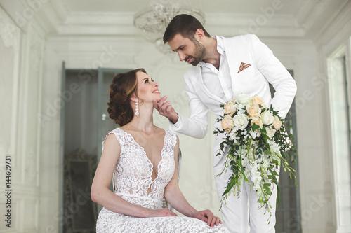 Fényképezés  Chic wedding couple groom and bride posing in a white Studio