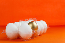 Transparent Packaging Of Chicken Eggs With One Golden Egg On An Orange Background.